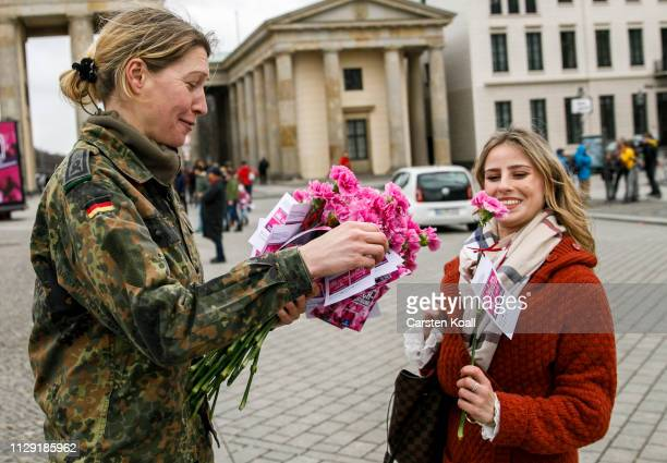 A soldier of the Bundeswehr hands out a carnation to a passerby in front of the Landmark Brandenburg Tor on International Women's Day on March 8 2019...