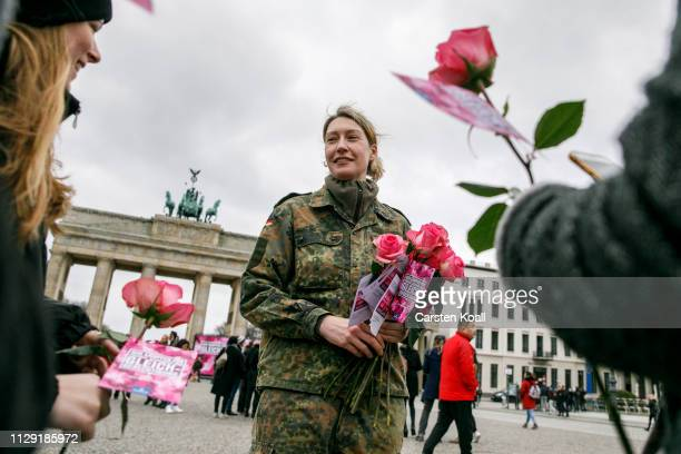 A soldier of the Bundeswehr hands out carnations to passerby in front of the Landmark Brandenburg Tor on International Women's Day on March 8 2019 in...