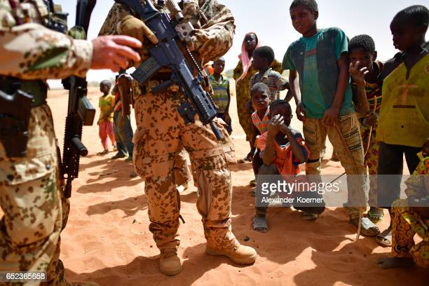 A soldier of the Bundeswehr the German Armed Forces holds its G36 rifle while being watched by children after leaving a weekly cattle market on the...