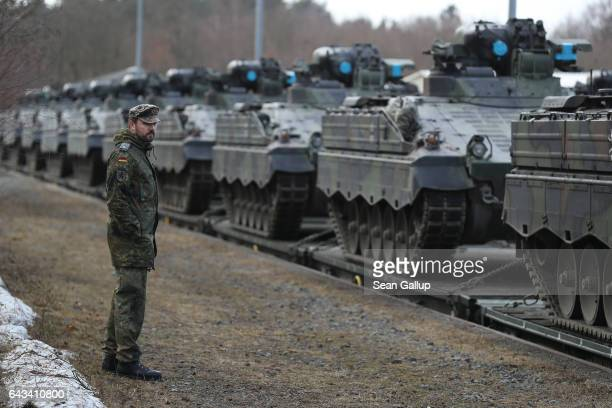 A soldier of the Bundeswehr the German armed forces looks at Marder light tanks after they had been loaded onto trains for transport to Lithuania on...