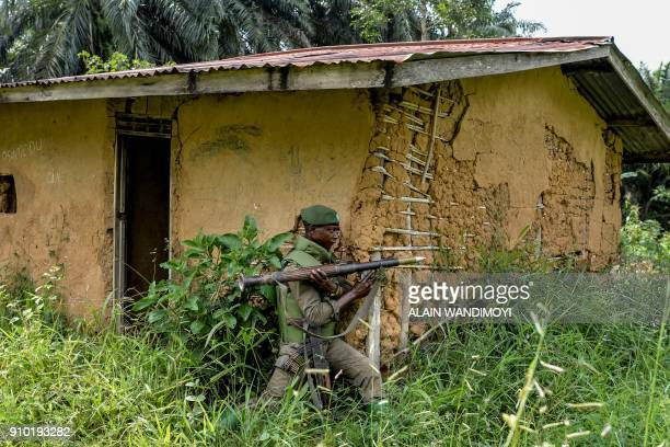A soldier of the FARDC takes cover during exchanges of fire with members of the ADF in Opira North Kivu on January 25 2018 / AFP PHOTO / ALAIN...