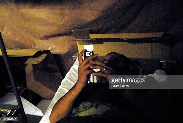 A soldier of the Folgore Parachute Brigade texts with his mobile phone in his tent at night time on September 16 2009 in Shindand Military Base...