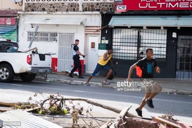 TOPSHOT A soldier of the French Gendarmerie chases alleged looters as the run past the devastation from hurricane Irma on the French island of...