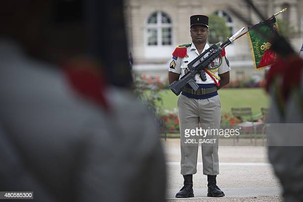 A soldier of the French Legion Etrangere from the 3rd REI based in Kourou French Guiana stands at attention as others Legionnaires play music with...