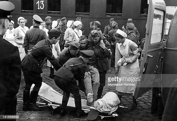 Soldier of the German army is moved onto an ambulance stretcher, after being wounded in Kutno. Poland, September 1939