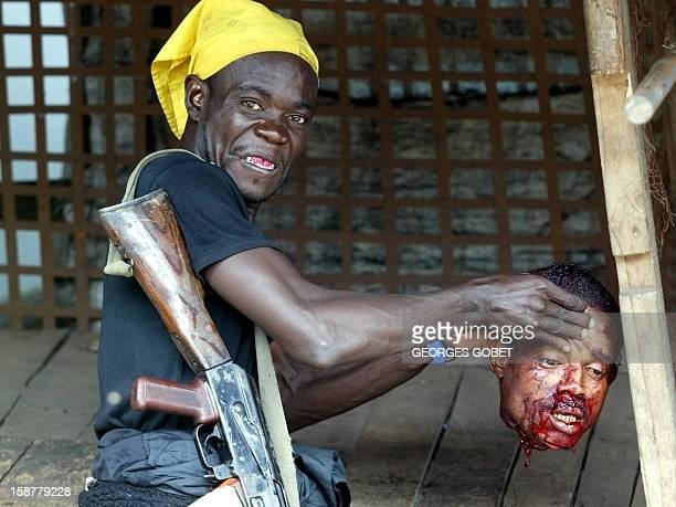 A soldier of the government forces shows the decapitated head of a LURD rebel soldier 21 July 2003 killed during the heavy fighting for control of...