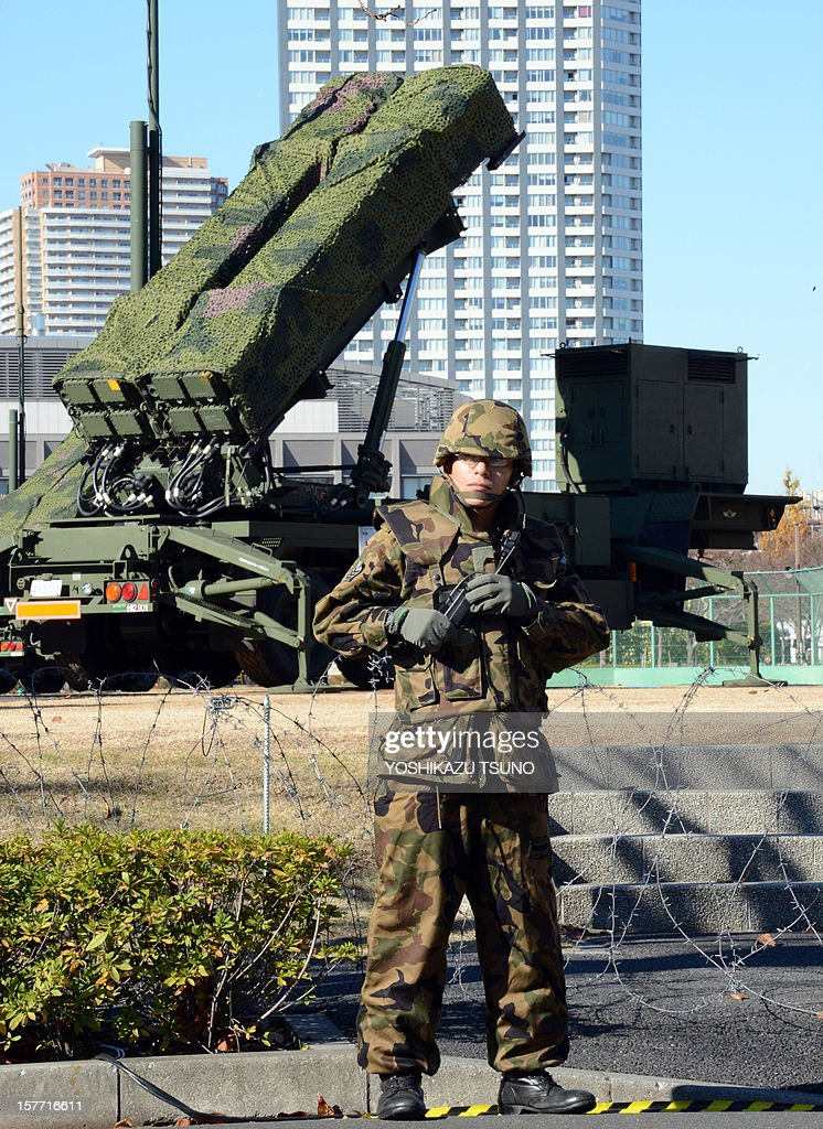 A soldier of the Ground Self-Defense Force (SDF) stands guard in front of Japan's SDF set Patriot Advanced Capability-3 (PAC-3) missile launcher at the Defence Ministry in Tokyo on December 6, 2012. Japan on December 6 dispatched three destroyers to waters over which North Korea says its satellite-bearing rocket will travel. In Tokyo, the defence ministry has deployed another PAC-3 battery at its headquarters as part of its effort to intercept anything headed towards the Japanese mainland. AFP PHOTO / Yoshikazu TSUNO