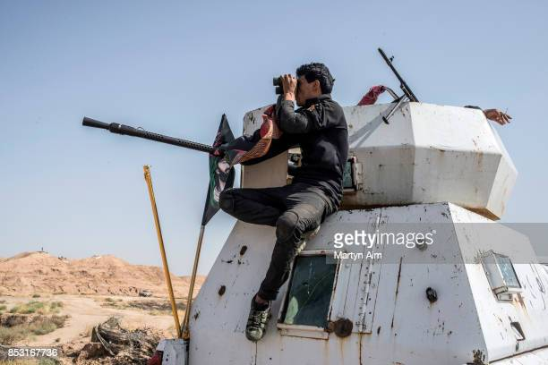A soldier of the Hashd AlShaabi looks through binoculars during an offensive to drive out Islamic State militants on September 24 2017 in Hawija Iraq...