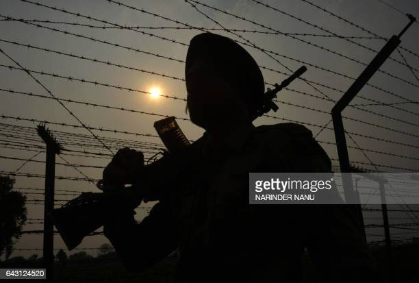 TOPSHOT A soldier of The Indian Border Security Force is silhouetted against the sun as he takes part in a patrol along a fence at the IndiaPakistan...