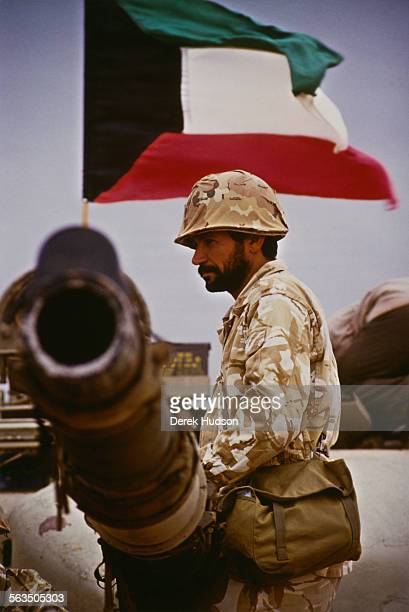 A soldier of the InterArab Force in Saudi Arabia during the Gulf War 1990 The flag of Kuwait is flying behind him