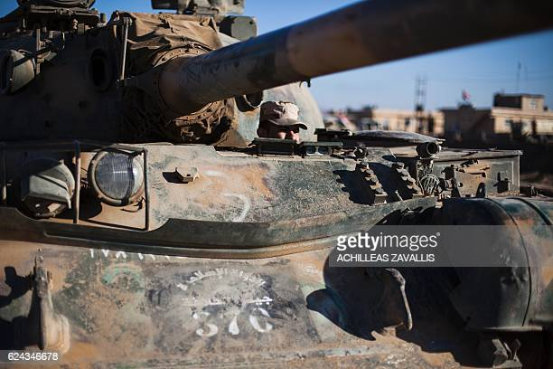 Soldier of the Iraqi army's 9th armoured division sits inside a tank left behind by retreating Islamic State militants, outside a base of the Iraqi...