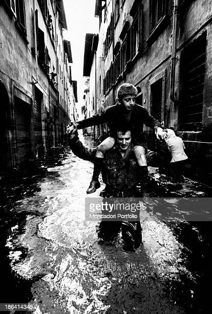A soldier of the Italian Army rescues a boy by carrying him on his shoulders through a street of the old town of the city not far from Palazzo...