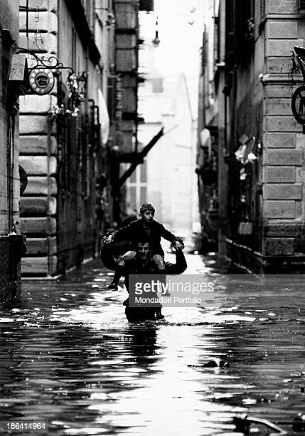 A soldier of the Italian Army rescues a boy by carrying him on his shoulders in a street of the old town not far from Palazzo Vecchio where the water...