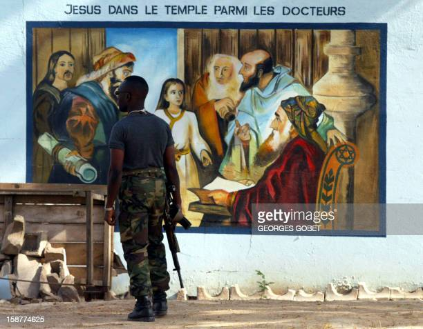 Soldier of the Ivorian Patriotic Movement stands guard outside the Bouake cathedral as the MPCI's political delegation, attends the Sunday mass 02...