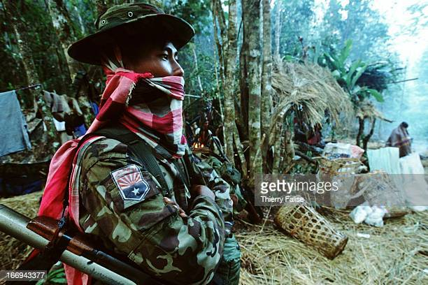 A soldier of the Karen National Liberation Army stands in a jungle camp during a freezing morning