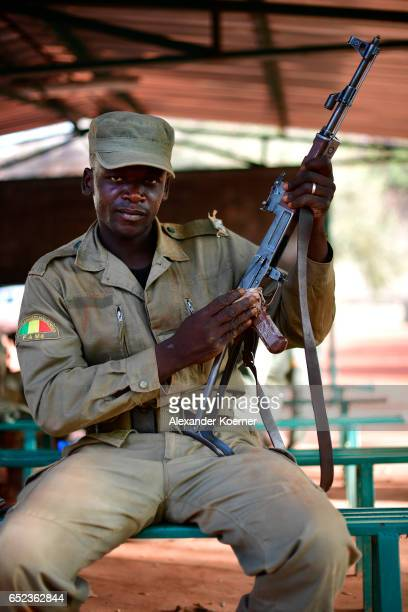 A soldier of the Malian Armed Forces poses for a photograph while cleaning his AK47 on March 9 2017 in Koulikoro Mali The training is part of a...