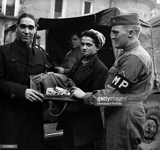 US soldier of the Military Police pulling in two young guys who are selling American cigarettes on the black market Naples November 1944