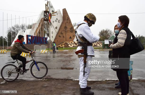 Soldier of the National Guard wearing face mask checks documents at a checkpoint set up outside Bishkek as the city is on lockdown to prevent the...