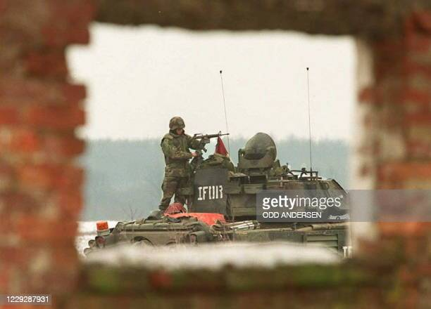 """Soldier of the NATO peace implementation cleans 02 January his M-16 assault rifle on top of a tank at a US base """"Bandit camp"""" outside the village of..."""
