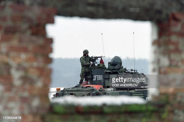 """Soldier of the NATO peace implementation cleans on January 02, 1996 his M-16 assault rifle on top of a tank at a US base """"Bandit camp"""" outside the..."""