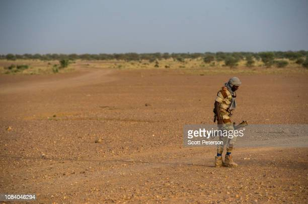A soldier of the Niger National Guard carries his gun across the desert while protecting a convoy crossing the Sahara Desert from Niger north to...