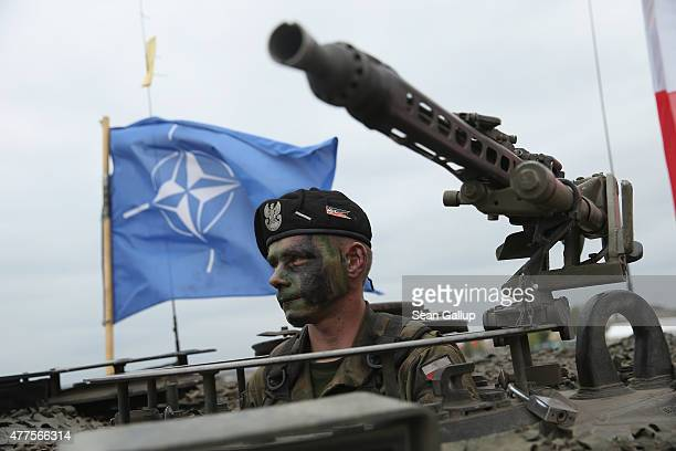 A soldier of the Polish Army sits in a tank as a NATO flag flies behind during the NATO Noble Jump military exercises of the VJTF forces on June 18...
