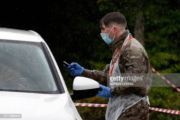 Soldier of the Royal Welsh regiment communicates via mobile phone through the closed window of a key worker's vechile at a drive-in testing facility...