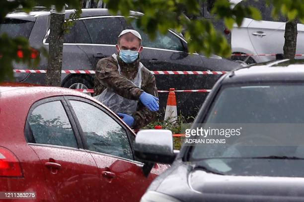 A soldier of the royal Welsh regiment directs traffic as key workers queue at a drivein testing facility for the novel coronavirus COVID19 in...