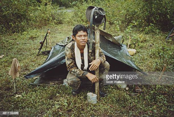 A soldier of the Sandinista Popular Army crouching outside a bivouac Nicaragua 1985