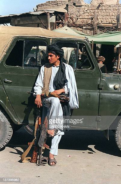 A soldier of the Taliban militia waits with three Kalashnikovs in front of the PuliKhisti mosque as his friends left for Friday prayer in Kabul on...