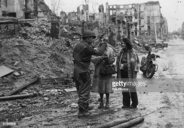 A soldier of the US First Army instructs two civilians to take cover Cologne Germany 7th March 1945