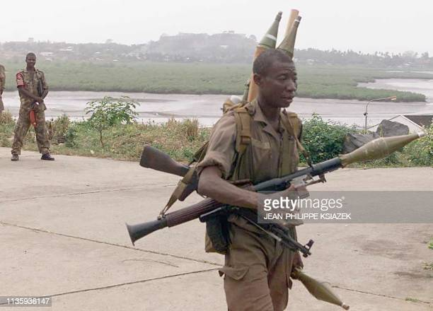 A soldier of the West African peacekeeping force ECOMOG is heavily loaded with rocketpropelled grenades 07 January at Freetown's Lungi airport Sierra...