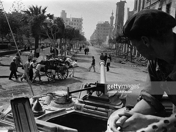 A soldier on board a tank looks out over an Egyptian street during the Suez Crisis Original Publication Picture Post 8735 Death Wore A Galabiya pub...