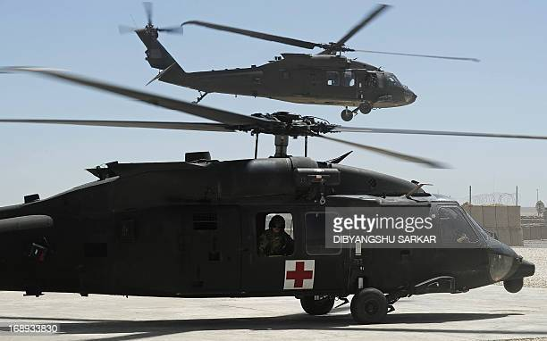 A US soldier on board a UH60 Black Hawk medevac helicopter of the 10th Combat Aviation Brigade looks on from his aircraft as another helicopter flies...