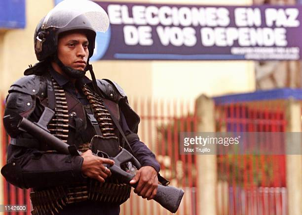 A soldier on guard at the National Stadium stands in front a banner reading Peaceful elections depends on you November 2 2001 in Managua Nicaragua...
