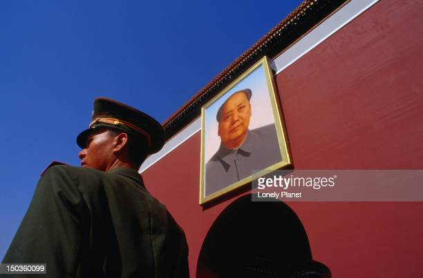 Soldier on guard in front of the Gate of Heavenly Peace and portrait of Mao Zedong in Tiananmen Square.