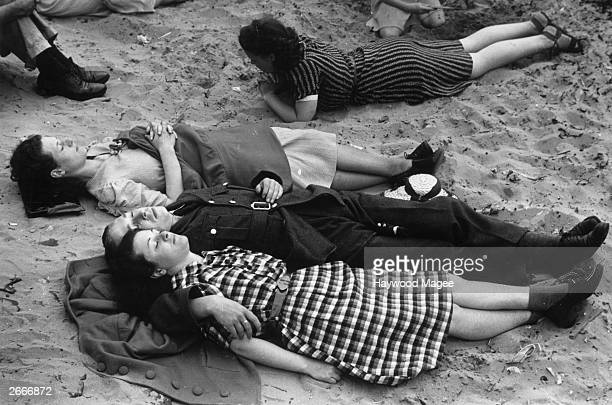 A soldier on leave from his wartime duties lying on the beach with his girlfriend at the Lancashire resort of Blackpool Original Publication Picture...