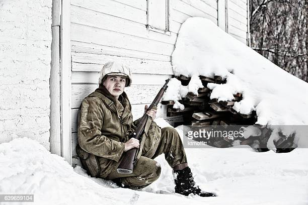 WWII US Soldier On Watch Leaning Against Barn in Winter