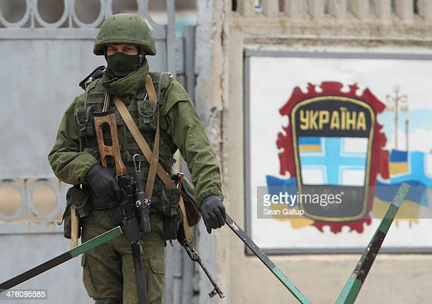 A soldier one of several hundred who had taken up positions around a Ukrainian military base stands at one of the base's entrance gates in Crimea on...