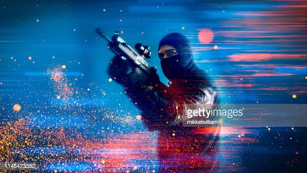soldier or criminal from video game holds a machine gun and aims at a target - terrorism stock pictures, royalty-free photos & images