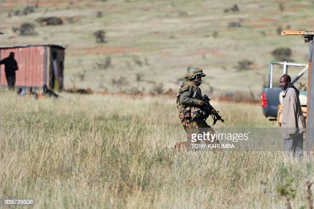 A soldier overruns a mock insurgent training camp during a simulated military excercise of the British Army Training Unit in Kenya together with the...