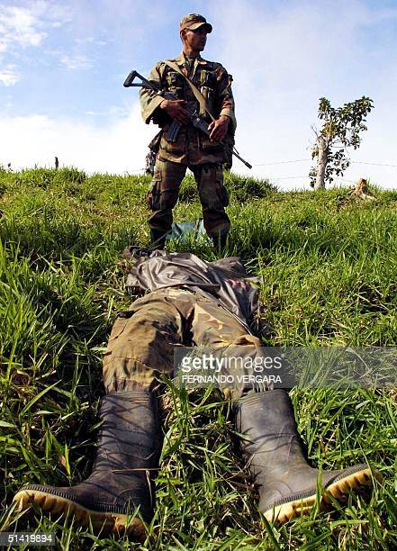 A soldier participating in the 'Columbia' excercise guards one of the 12 guerillas from the Fuerzas Armadas Revolucionarias de Columbia that died in...