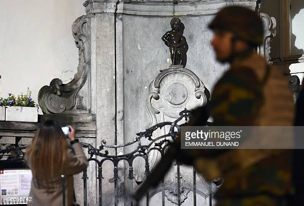 A soldier patrols around a security perimeter next to a tourist taking a photo of the Manneken Pis statue as a reported police intervention takes...