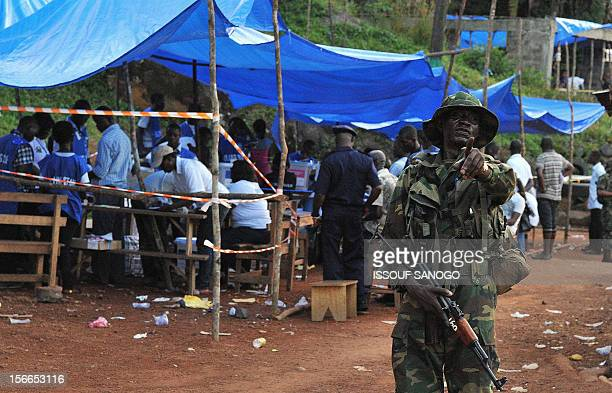 A soldier patrols as election scrutineers count ballots at a polling station during the national presidential parliamentary and local elections in...