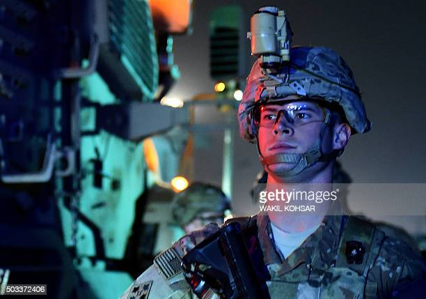A US soldier patrols next a military vehicle as he arrives at the site of a suicide car bomb attack that targeted a compound for foreign contractors...