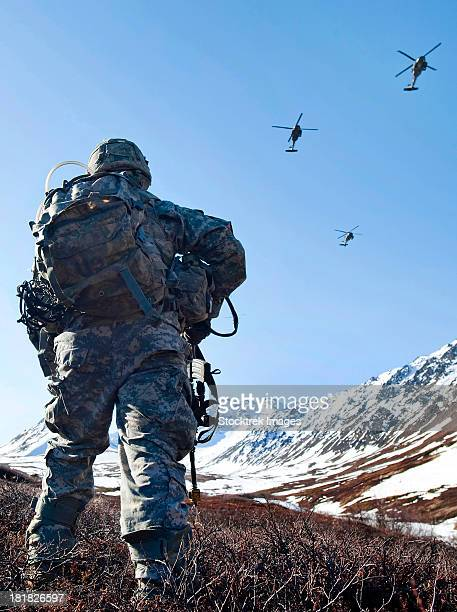 soldier patrols through alaska's chugach range as uh-60 black hawk helicopters fly above. - military attack stock pictures, royalty-free photos & images