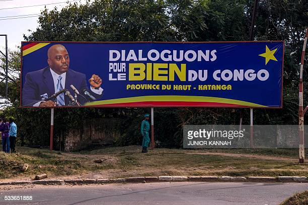 A soldier patrols under a billboard featuring Democratic Republic of Congo's President Joseph Kabila reading 'Let's talk for the good of the Congo'...