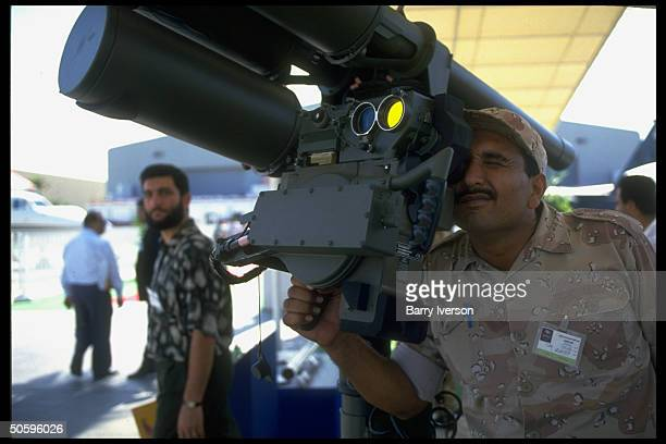 Soldier peering through viewfinder of unident weapons system among civilian mil aircraft arms displays at Dubai Air Show