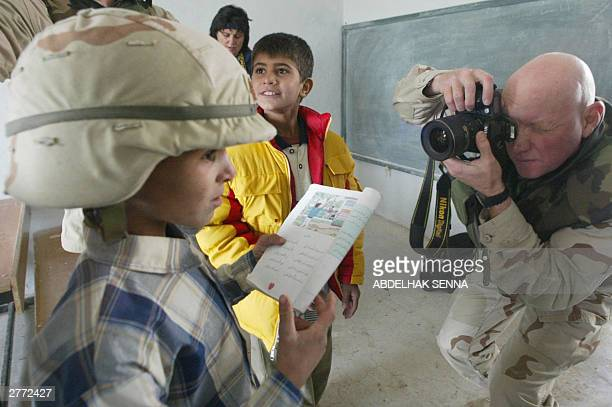 US soldier photographs an Iraqi schoolboy wearing his helmet during the reopening ceremony of the alZohur school outside the southern Iraqi city of...
