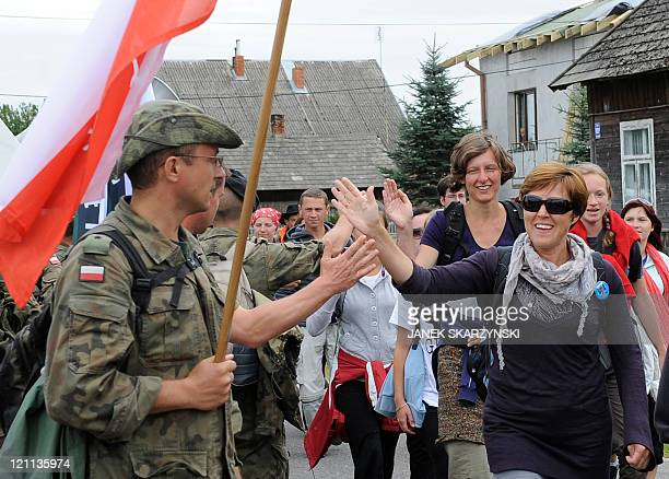 Soldier pilgrims greet other pilgrims walking to the Marian shrine of Czestochowa on August 14 2011 in southern Poland For 300 years thousands of...